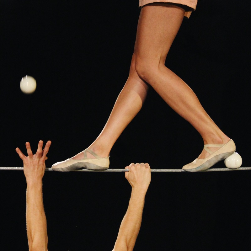 Scaled   jeromy zwick  liisa na ykki s feet legs on the tightwire and jeromy zwick s hands from the bottom reaching for ball